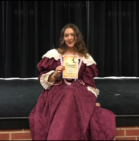 Roxane, played by Alexia Stearns, poses with a program.