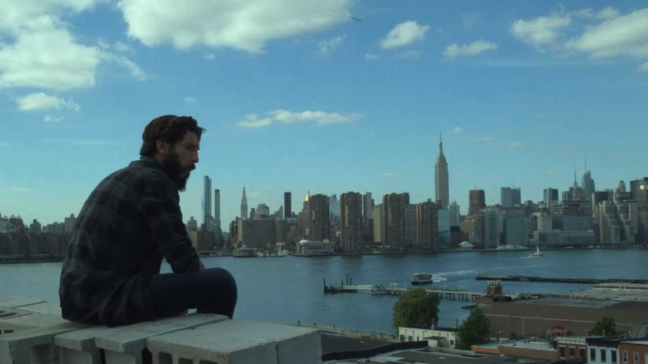 Frank Castle, The Punisher, sits on the edge of a rooftop and eats a sandwich.
