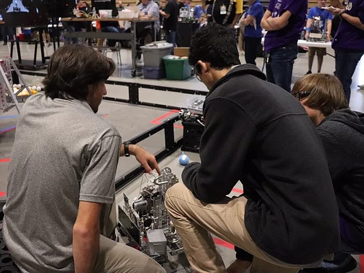 Members of Fortissimus inspect their robot after a match.