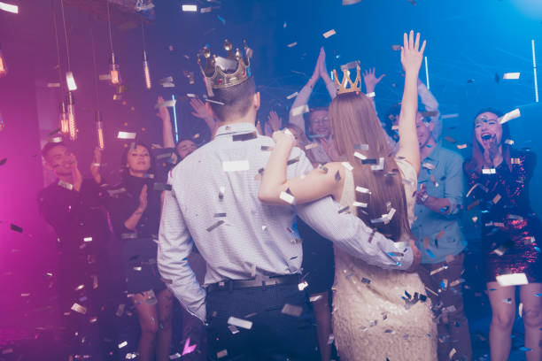 Back rear photo of charming, lovers mates raise hand wear dress suit formalwear disco discotheque high-school event